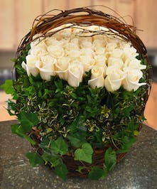 Indulge her in a garden of over 48 dozen fresh cut roses nestled within a charming, brown wicker basket.
