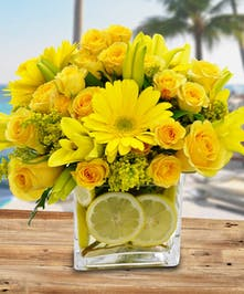 Brighten up their day with this sweet arrangement of yellow roses, lilies, gerbera daisies and lemon accent.
