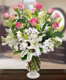 Featuring a dozen pink roses, white orchids, white lilies and white stock in a beautiful Charlotte vase