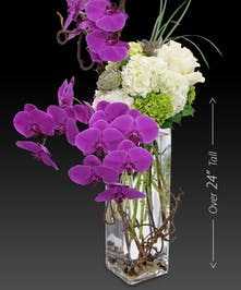 "A design that will ""wow"" and impress with its height and artful placement of purple orchids among curly willow, white hydrangea and succulents."