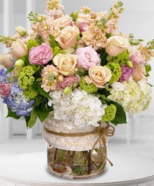 Premium floral varieties of roses, hydrangea, greens and more are filled in a glass vase bearing a designer ribbon.