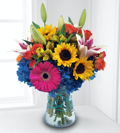 This bouquet is unforgettable with its vivid display of vibrant blooms.
