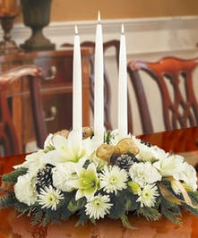 This winter white centerpiece features taper candles, pine cones & more!
