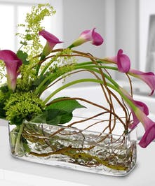 Sleek and elegant pink calla lilies are cascading over this rectangular vase filled with gem stones.