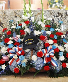 Honor that special Patriot with this sprawling flow of red, white and blue flowers, ribbons, and flags. A true American tribute. (hat not included.)