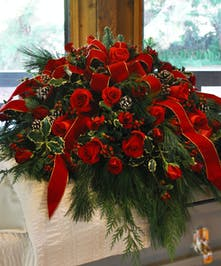 Breathtaking, vibrant red roses are featured in this one-of-a-kind funeral casket spray.