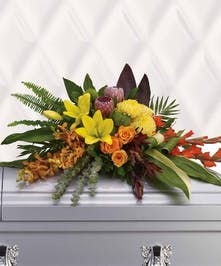 Tropical flowers evoke tropical breezes in this modern style casket spray.